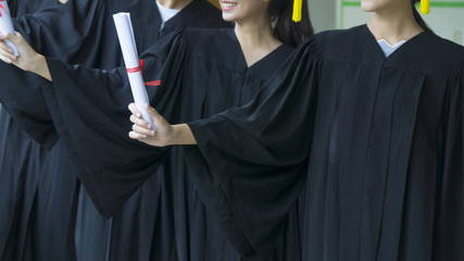 people with black graduation gowns hold diploma.