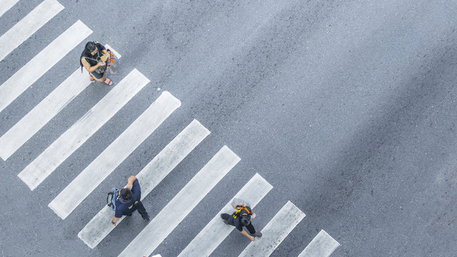 From the top view of people walk on street pedestrian crossroad in the city street with the motorcycle drives pass road ,bird eye view.