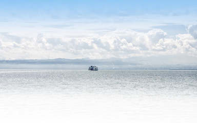 A lonely ferry boat crosses Bodensee lake (Lake Constance) from Germany to Switzerland
