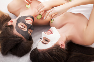 A picture of two girls friends relaxing with facial masks on over white background