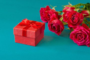 St. Valentines Day concept. Fresh red roses and gift box on wooden table