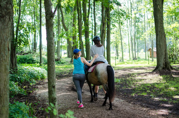 child horseback riding with a mentor in a green forest