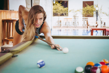 Beautiful woman is playing the billiards