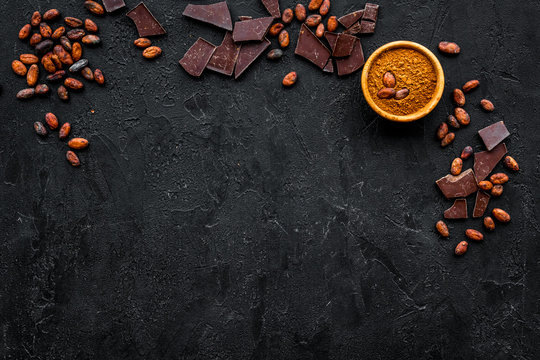 Chocolate and cacao concept. Cocoa powder in bowl near cocoa beans and broken chocolate on black background top view copy space