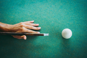 Woman's hand is ready to touch white ball with billiard cue.