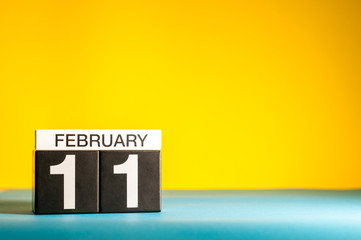 February 11th. Day 11 of february month, calendar on yellow background. Winter time. Empty space for text