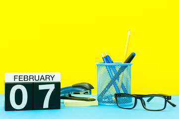 February 7th. Day 7 of february month, calendar on yellow background with office supplies. Winter time