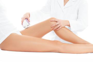 Beautician removing hair of woman's leg.  Laser depilation