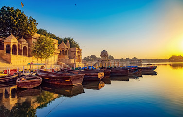 Fototapete - Gadisar lake (Gadi Sagar) Jaisalmer Rajasthan with ancient architecture and tourist boats at sunrise