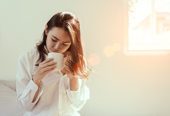 Asian woman drinking coffee in the morning breakfast on bed side window bedroom fresh start the day happiness relax at home healthy lifestyle concept