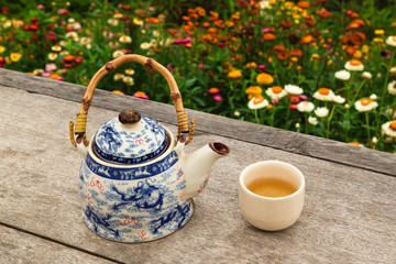 Chinese teapot and cup with green tea on a wooden table on a background of bright colorful flowers, top view. Pai, Thailand.