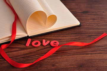 Pages of a book bend in a heart shape displayed with a red ribbon and the word love