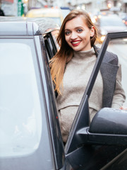 Pregnant beautiful young woman with car outdoor