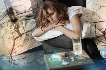 Deep depression. Upset young woman feeling gloomy while looking at her medication and sitting at home