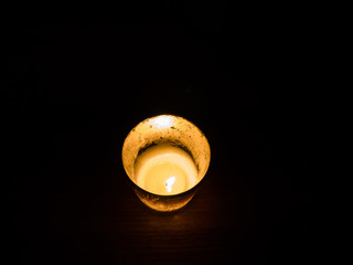 Candle on dark wooden table