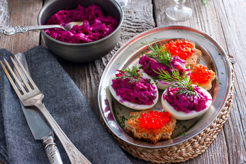 Stuffed eggs with beets and salted fish, horizontal