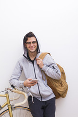 young with backpack and mobile phone on the white wall
