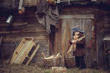 A little boy in an old coat collecting firewood in the yard