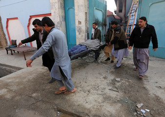 Afghan men carry a dead body one victim at the site of yesterdayÕs blast and gun fire in Jalalabad, Afghanistan