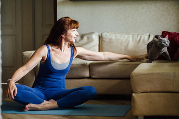 Mature woman in sportswear sitting on yoga mat and stroking cat. Truthful positive moment of life with real people model.