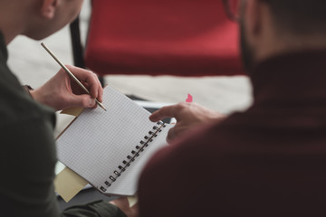 cropped image of man pointing on something in friends notebook in library