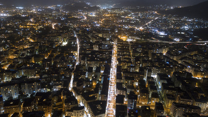 Aerial night view on the north part of the city of Naples, Italy. The streets are lit and surrounded by buildings and buildings.