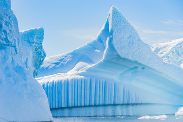 Antarctic icebergs and majestic landscape, sunny day, cloudy blue sky