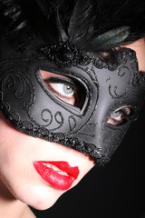 Junge Frau mit Federn Maske blickt in die Ferne