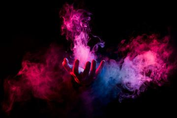 hand inside colorful smoke on black background