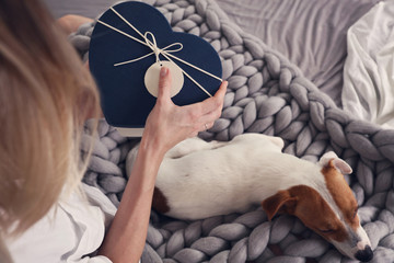 Woman opening present gift box , enjoying Cozy ,lazy day at home, cold weather, warm blanket. Dog sleeping on female feet. Relax, carefree, comfort lifestyle.