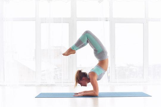 Young woman practicing yoga, standing in Vrischikasana Scorpion pose at the yoga studio