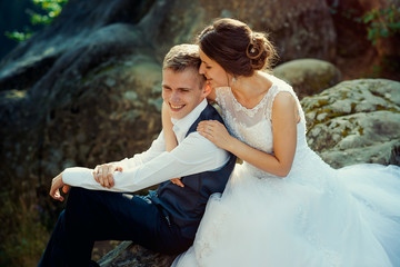 Sensitive portrait of the beautiful cheerful newlywed couple softly hugging on the rock.