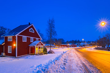 Winter scenery with red wooden house at night in Sweden