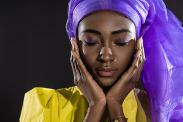 close-up shot of young african american woman in stylish wire head wrap isolated on black