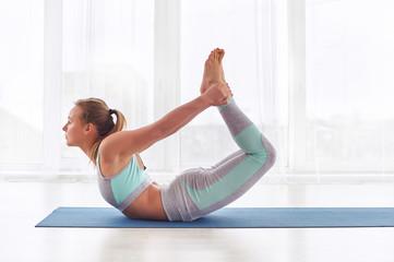 Beautiful woman practices yoga asana dhanurasana - bow pose at the yoga studio