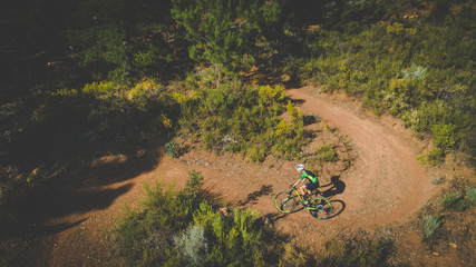 Aerial view of a mountain biker speeding downhill on a mountain bike track in the woods