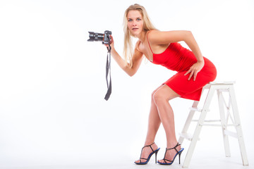 Girl with a camera. Blonde girl in a red dress. Girl photographer takes pictures. Girl learn to photograph. The camera is in the hands of a blonde.