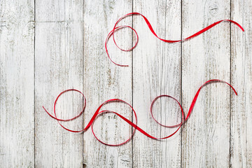 Red ribbons on the white wooden background