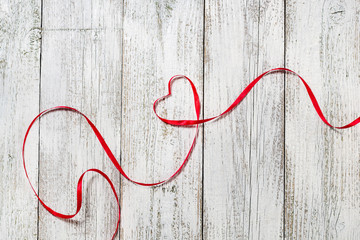 Happy Valentines Day. Red Ribbon Heart on white wooden background