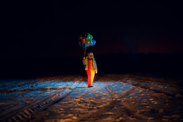 Full-length clown photo with colorful balloons at night