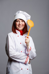 Photo of woman cook in white coat and cap with slotted spoon