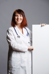 Picture of female doctor in white coat and with phonendoscope points finger at blank piece of paper