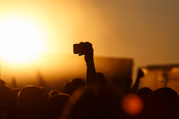 Silhouette of smartphone in a hand over crowd