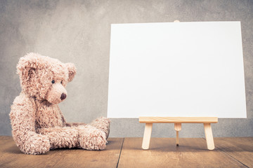 Sitting old Teddy Bear toy near portable desk easel for painting with canvas blank front concrete wall background. Retro old style filtered photo