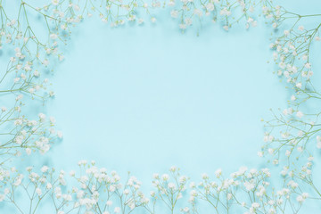 Floral greeting card for the spring holidays with copy space. Delicate small white flowers in a turquoise blue background, top view, mock up