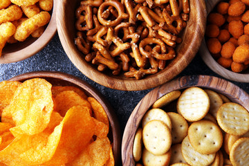 Salty snacks. Pretzels, chips, crackers in wooden bowls. Fototapete