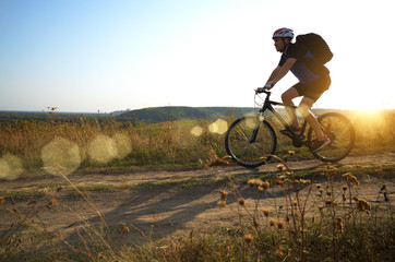 Male cyclist with backpack driving by rural dirt road outdoors