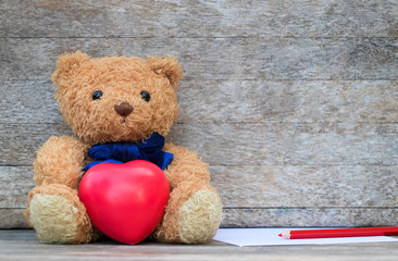 Brown bear wear blue necktie and sitting on the table with hug red heart next to is paper and red pencil for write texture. The backdrop is blackwood flooring. Valentine concept, Copy space.