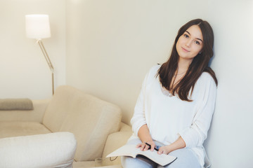 Pretty female with dark hair, holds diary, being busy with doing homework, writes essay while sits at domestic interior. Beautiful woman uses stationery, writes down creative ideas for project