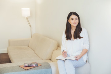 Successful intelligent female student makes plans for educational task, notes some ideas in notebook, sits at sofa, ponders about something pleasant. Woman writes report in her copybook